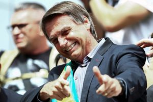 "Right-wing federal deputy and presidential candidate Jair Bolsonaro, gives a thumbs up to supporters during a rally at Afonso Pena airport in Curitiba, Brazil on March 28, 2018. Bolsonaro, who has repeatedly praised Brazil's two-decade-long military dictatorship, taunted Lula, calling him a ""bandit,"" and challenging him in Curitiba to see ""who can get the most people out on to the streets without paying them."" / AFP PHOTO / Heuler Andrey"